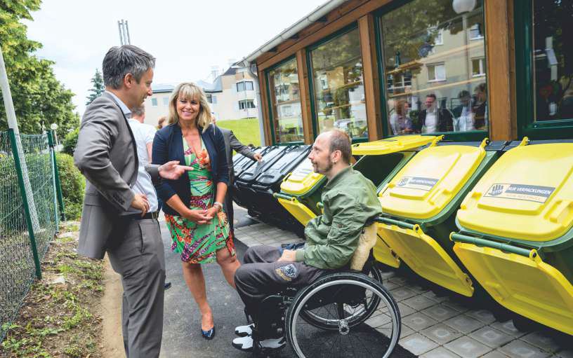 Ein Mann, eine Frau und ein Rollstuhlfahrer vor den neuen barrierefreien Mülltonnen in der Wohngemeinschaft Algersdorf.