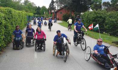 Eine Gruppe Rollstuhl- und Radfahrer rollt gemeinsam durch die Umwelt.
