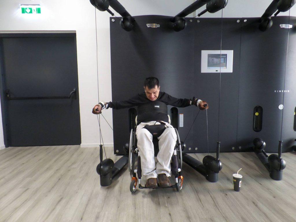 Rollstuhlfahrer trainiert in seinem Rollstuhl im barrierefreien Fitnesscenter.