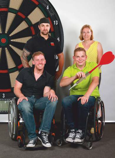 Vier Personen sind vor einer großen Dartscheibe, zwei davon im Rollstuhl. Einer der Rollstuhlfahrer hat einen übergroßen Dartpfeil in der Hand.