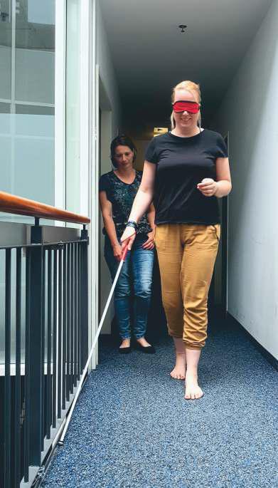 Eine Frau geht mit Augenbinde und Blinden Taststock begleitet einen Weg entlang.
