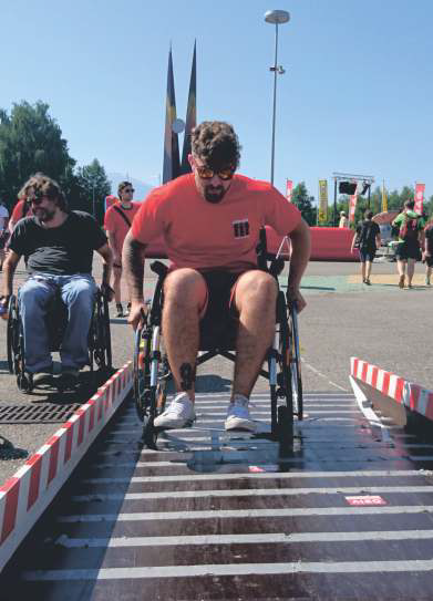 Junger Mann rollt auf einem Rollstuhl über den Rollstuhlparcour.